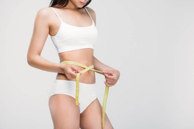 cropped view of slim girl in underwear measuring her waistline, isolated on grey