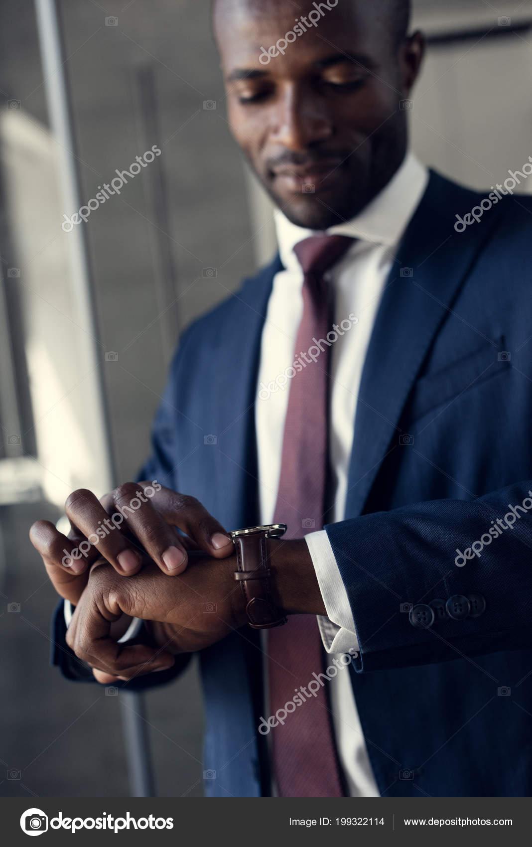 Primer plano retrato de hombre de negocios joven guapo traje elegante  mirando el reloj de pulsera — Foto de AllaSerebrina 1aa1e8e38eb5
