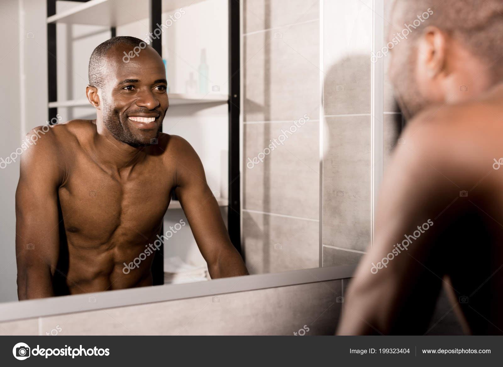 happy young man looking mirror bathroom stock photo