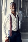 Photo handsome young businessman in white shirt with tie hanging on shoulders at bathroom