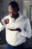 Fotografie hübscher junger Geschäftsmann in weißen Hemd Tasse Kaffee zu genießen