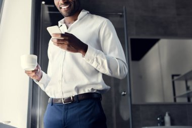 cropped shot of smiling young businessman in white shirt using smartphone during coffee break