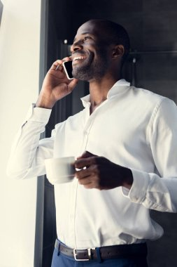 bottom view of handsome young businessman in white shirt talking by phone during coffee break