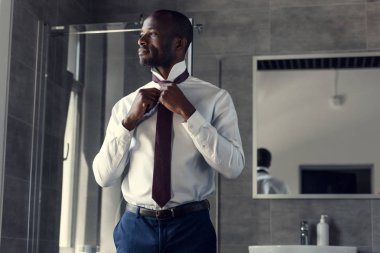 Handsome young businessman in white shirt putting on his tie at bathroom stock vector