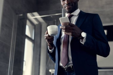 bottom view of handsome young businessman with cup of coffee using smartphone in bathroom