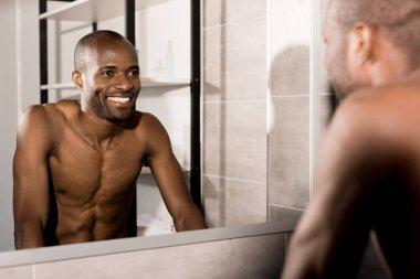 happy young man looking at mirror in bathroom