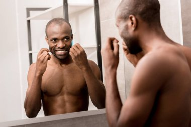 happy young man cleaning teeth with dental floss while looking at mirror in bathroom