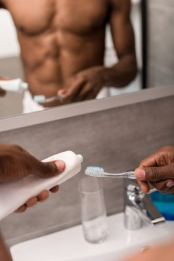 cropped shot of man applying toothpaste onto brush in front of mirror