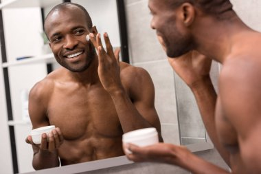 smiling young man applying facial cream while looking at mirror in bathroom