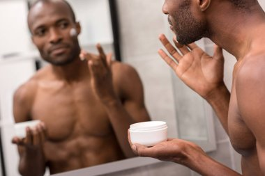 handsome young man applying facial cream while looking at mirror in bathroom