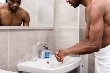 cropped shot of young african american man in towel washing hands in bathroom