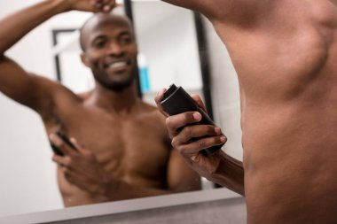 smiling young african american man holding deodorant spray and looking at mirror in bathroom