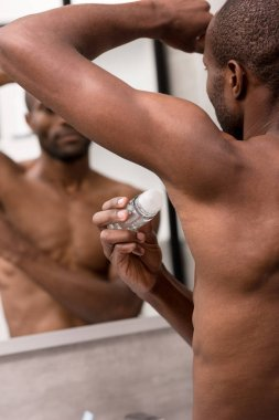 cropped shot of bare-chested african american man holding antiperspirant in bathroom
