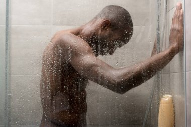 side view of handsome young african american man washing body in shower