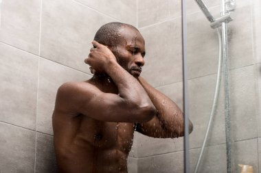 handsome african american man taking shower