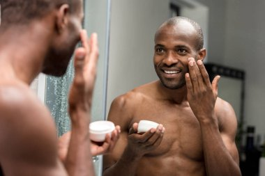 cropped shot of smiling young african american man applying facial cream and looking at mirror in bathroom