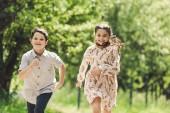 usmívající se děti baví a běží v letním parku