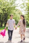 Fotografie usmívající se děti drží za ruce a procházky parkem