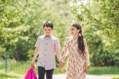 Fotografie rozkošné děti drželi se za ruce a procházky parkem
