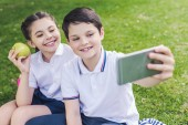 Happy školáci s selfie zatímco sedí na trávě v parku