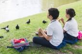 entzückende Schulkinder sitzen auf Gras und füttern Vögel