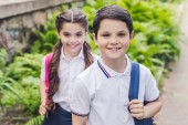 Fotografie adorable schoolchildren with backpacks looking at camera in park