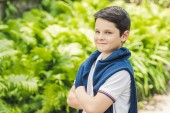 Photo stylish kid with jumper over shoulders looking at camera with crossed arms