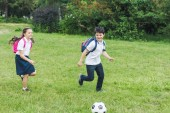 Photo schoolchildren with backpacks playing soccer together on meadow in park