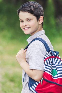 Close-up portrait of happy schoolboy with backpack looking at camera stock vector