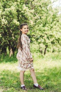 happy child in stylish dress posing in summer park