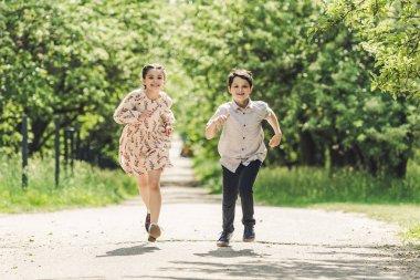 happy kids having fun and running in summer park