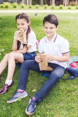 adorable schoolchildren sitting on grass and eating sandwiches
