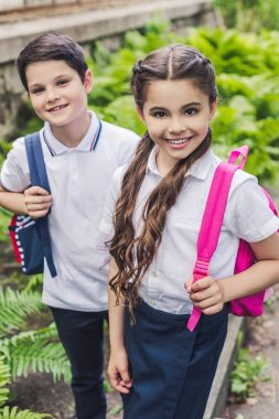 schoolchildren with backpacks looking at camera in park