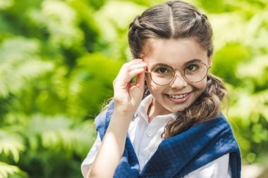 close-up portrait of schoolgirl in white shirt and jumper over shoulders looking at camera through stylish eyeglasses