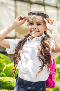 happy schoolgirl in stylish eyeglasses looking at camera