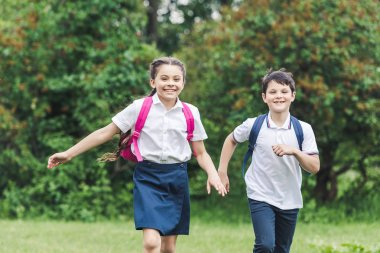 happy schoolchildren with backpacks running by park