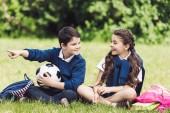 šťastné děti sedí na trávě v parku s batohy a fotbalový míč a chatování