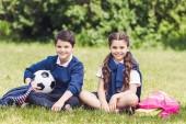 šťastné děti sedí na trávě v parku s batohy a fotbalový míč