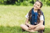 Fényképek ül a fűben park gyönyörű preteen iskoláslány