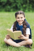 smiling schoolgirl with book sitting on grass in park and looking at camera