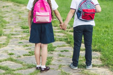 cropped shot of schoolchildren walking by pathway in park and holding hands