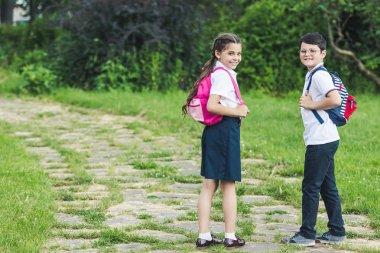 happy schoolchildren spending time together in park