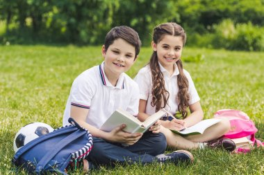 smiling schoolchildren doing homework together while sitting on grass in park and looking at camera
