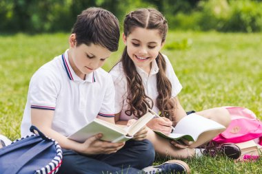 cute schoolchildren doing homework together while sitting on grass in park