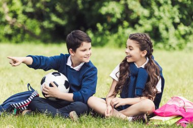happy schoolchildren sitting on grass in park with backpacks and soccer ball and chatting