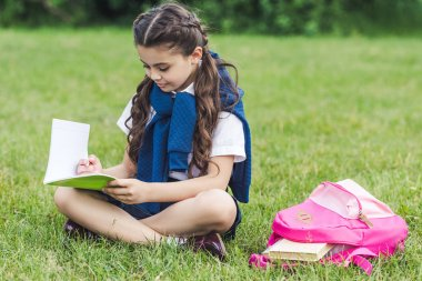 smiling schoolgirl reading book while sitting on grass in park