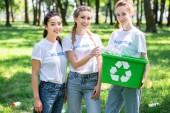 Fotografia belle donne volontarie con il riciclaggio in piedi casella nel parco