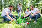 Fotografia giovani volontari con riciclaggio verde scatola pulizia parco insieme