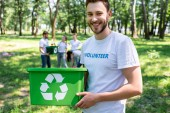 Photo young smiling volunteer with green recycling box in park with friends on background
