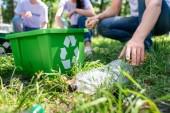 oříznutý pohled dobrovolníků s recyklačním box čištění trávníku dohromady